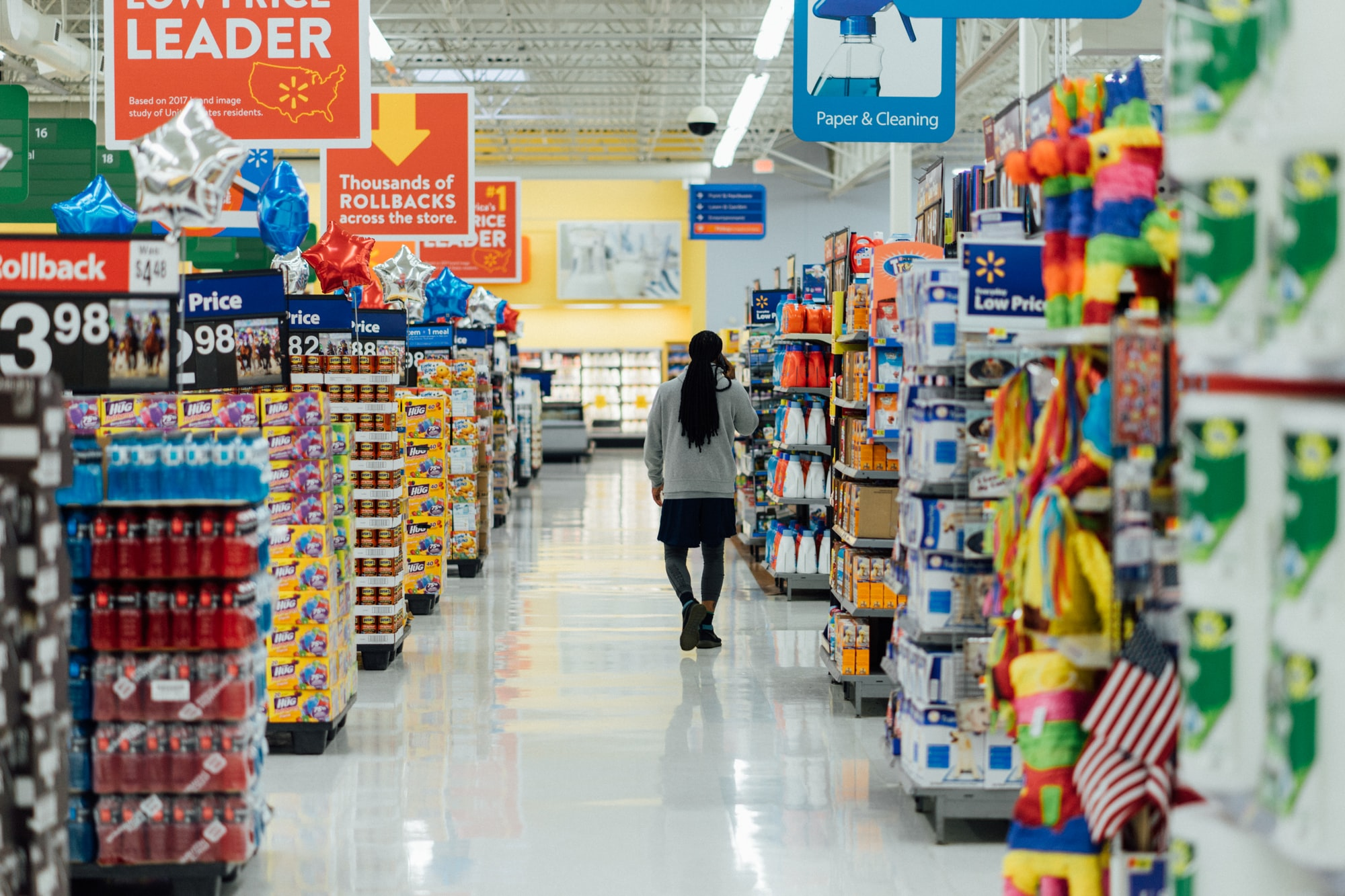 Woman walking down the aisles of Walmart. Join activists and organizers to make a difference on WeAct.