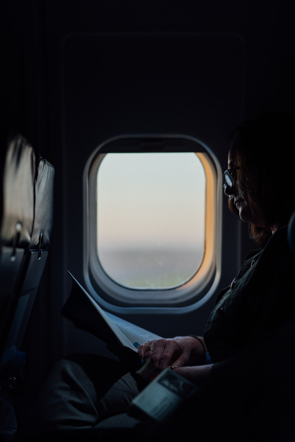 woman sitting and reading book on airliner