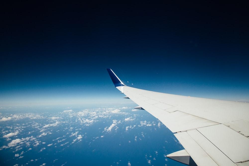 white airliner left wing flying in sky