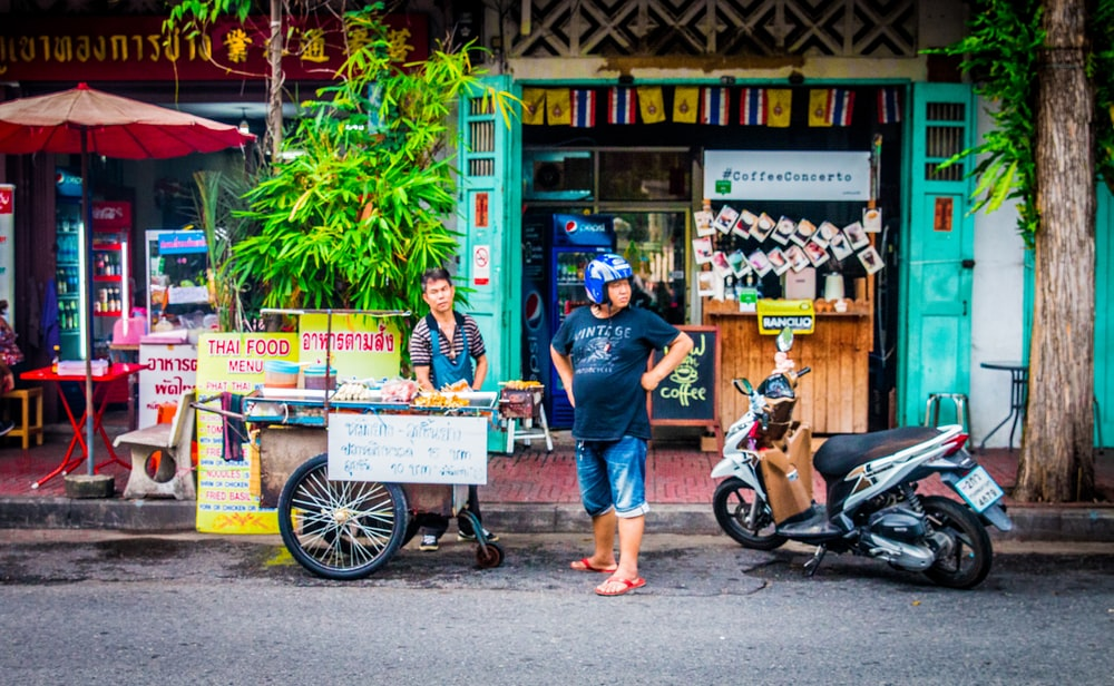 man wearing helmet standing between motorscooter and food cart