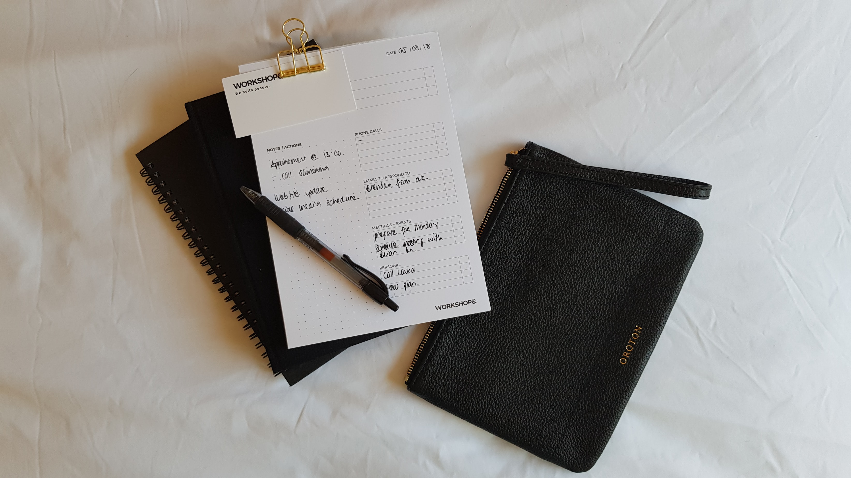 A note book with writing on it, on a white bed, with a small black purse next to it.