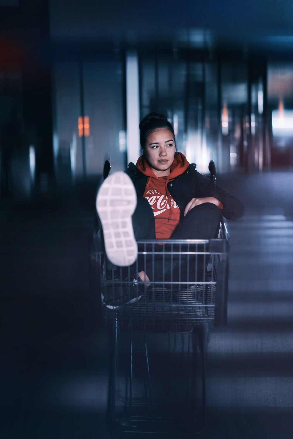 woman in red pullover hoodie sitting on gray rolling cart