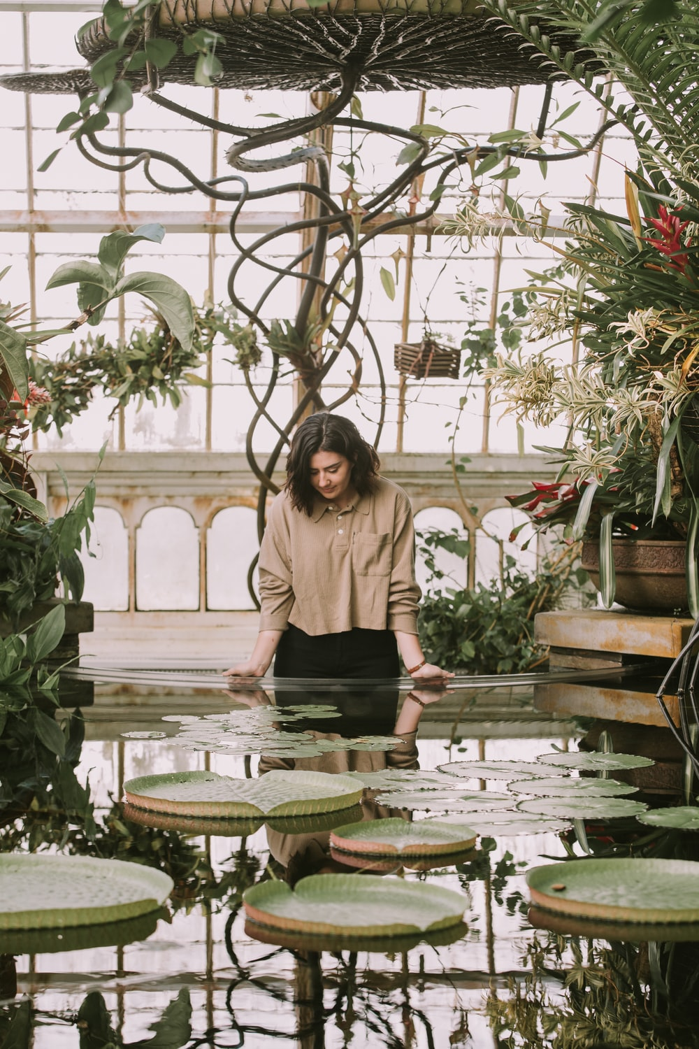 standing woman leaning on fountain with lily pads