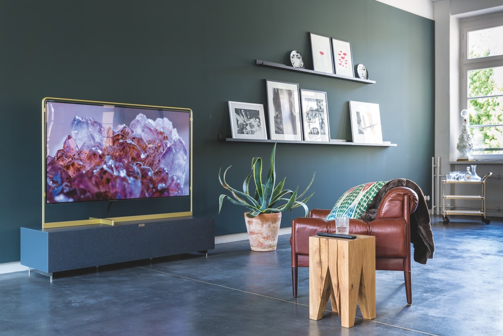 turned-on television in front of leather sofa chair