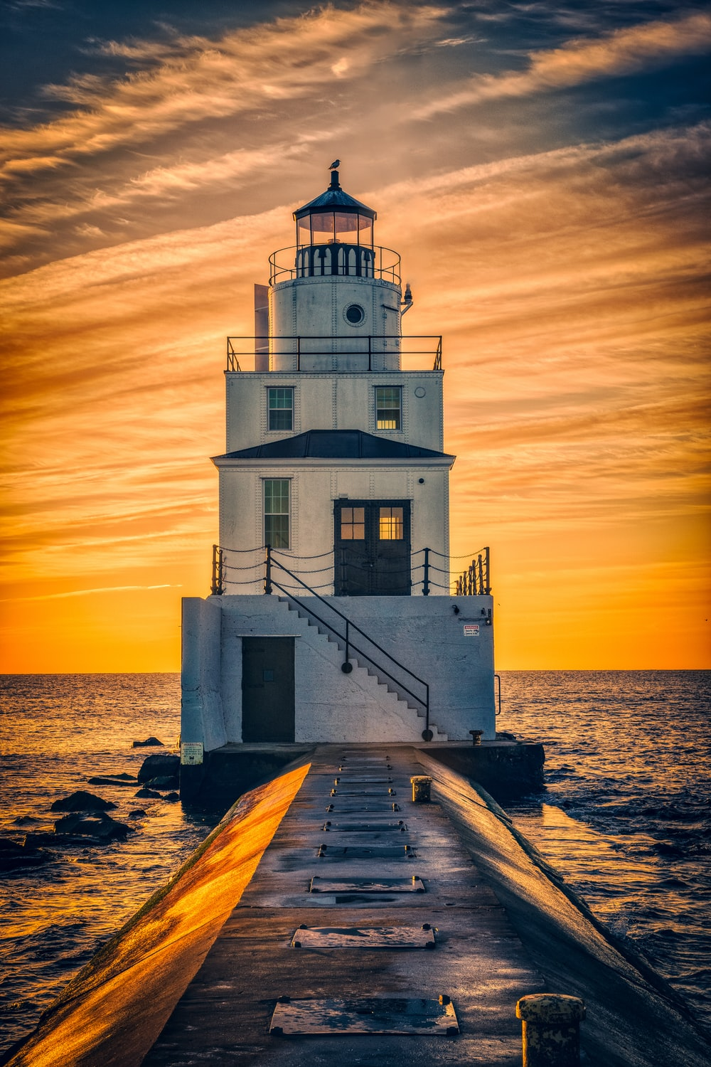 lighthouse surrounded by body of water during golden hour