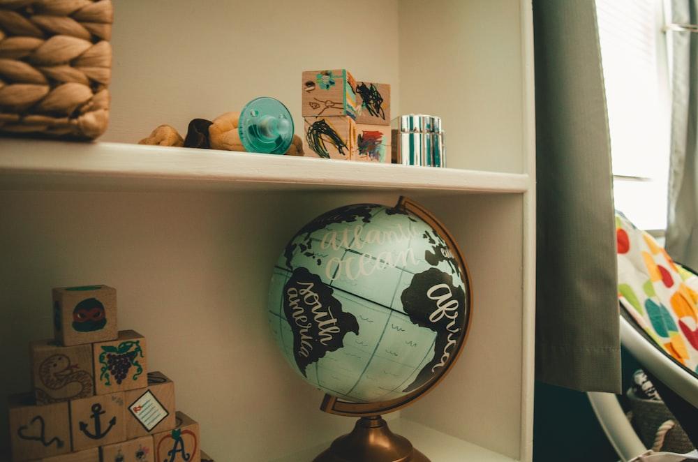 white and black desk globe on white wooden shelf