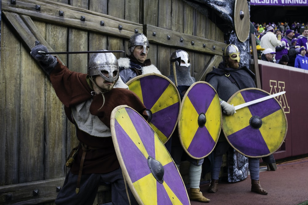 four men wearing armor holding sword and shield standing in front of wall