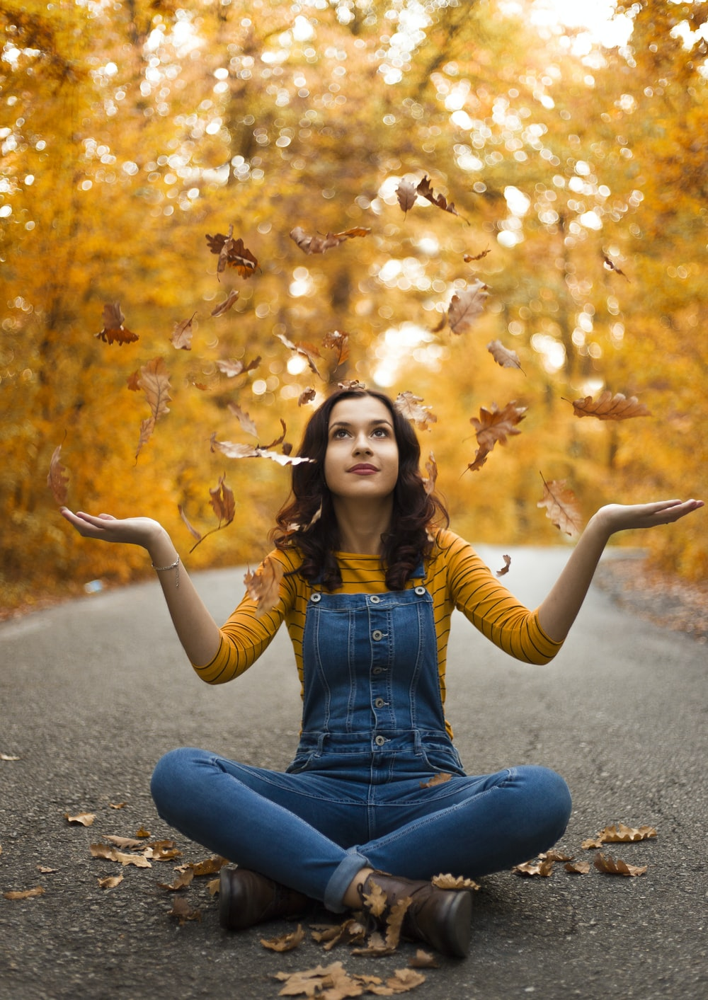 sitting person with crossed legs throwing leaves on air
