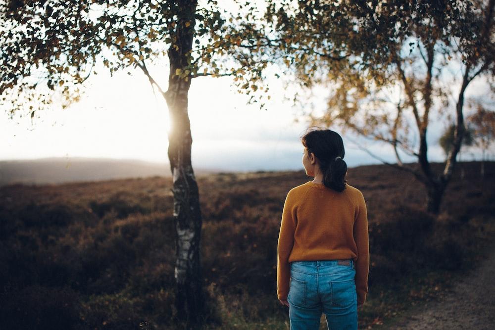 woman wearing brown sweater standing beside tree during daytime