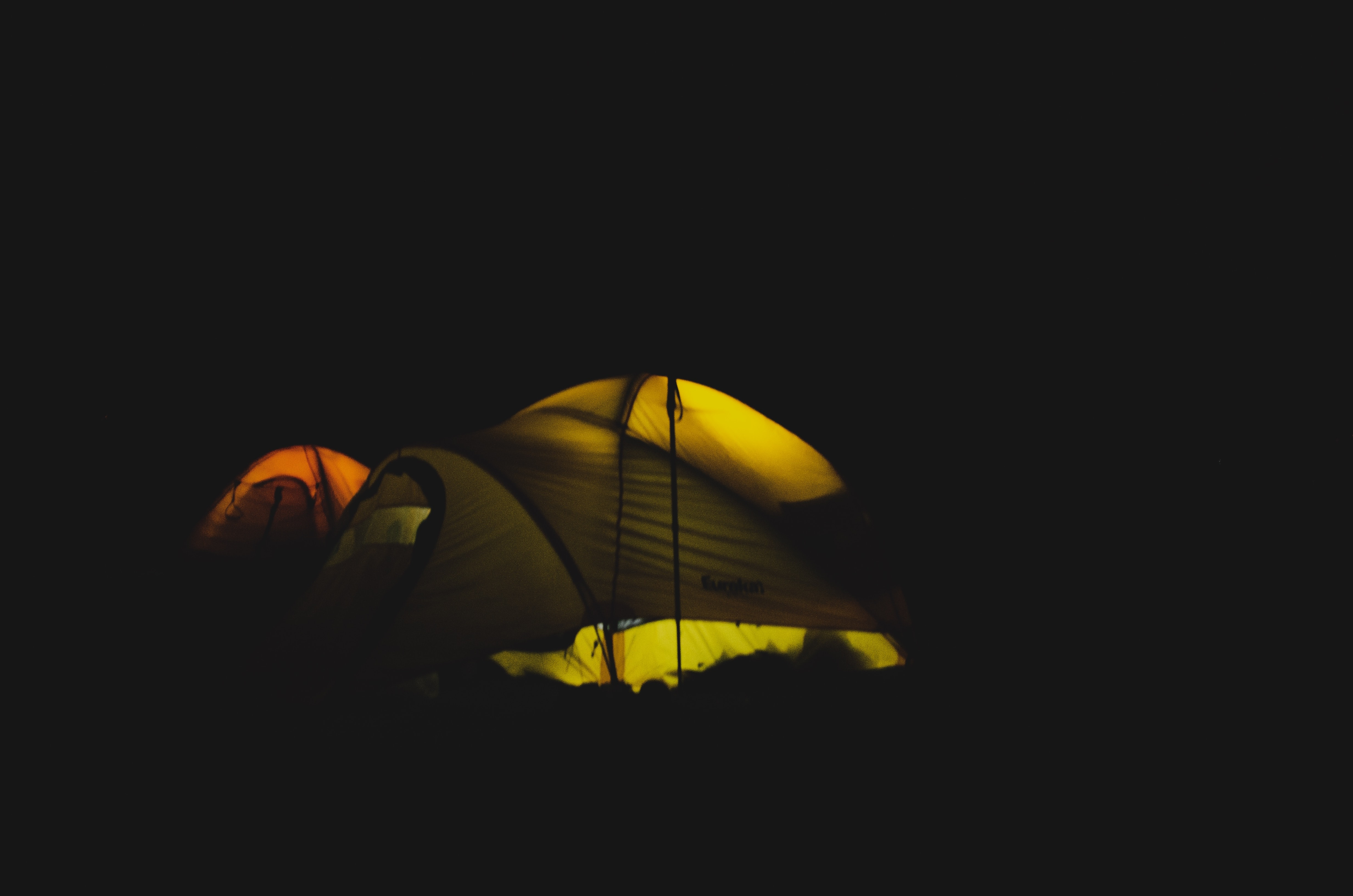 yellow and red dome tent with light at nighttime