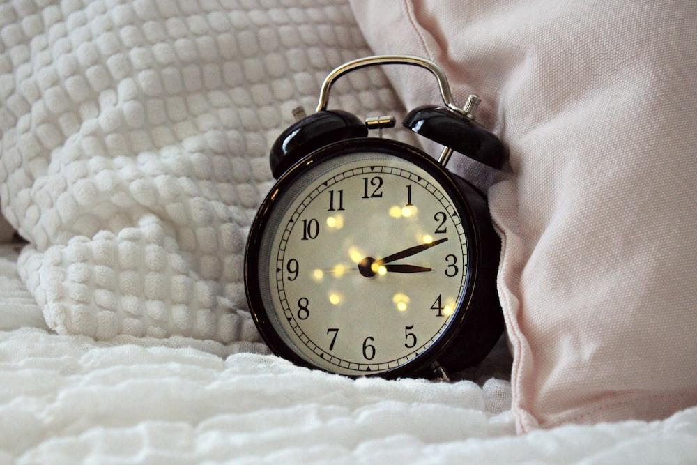 round black alarm clock displaying 3:12