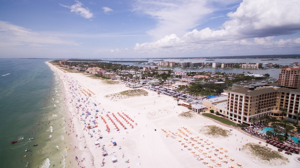 aerial photography of people on the beach across buildings at daytime