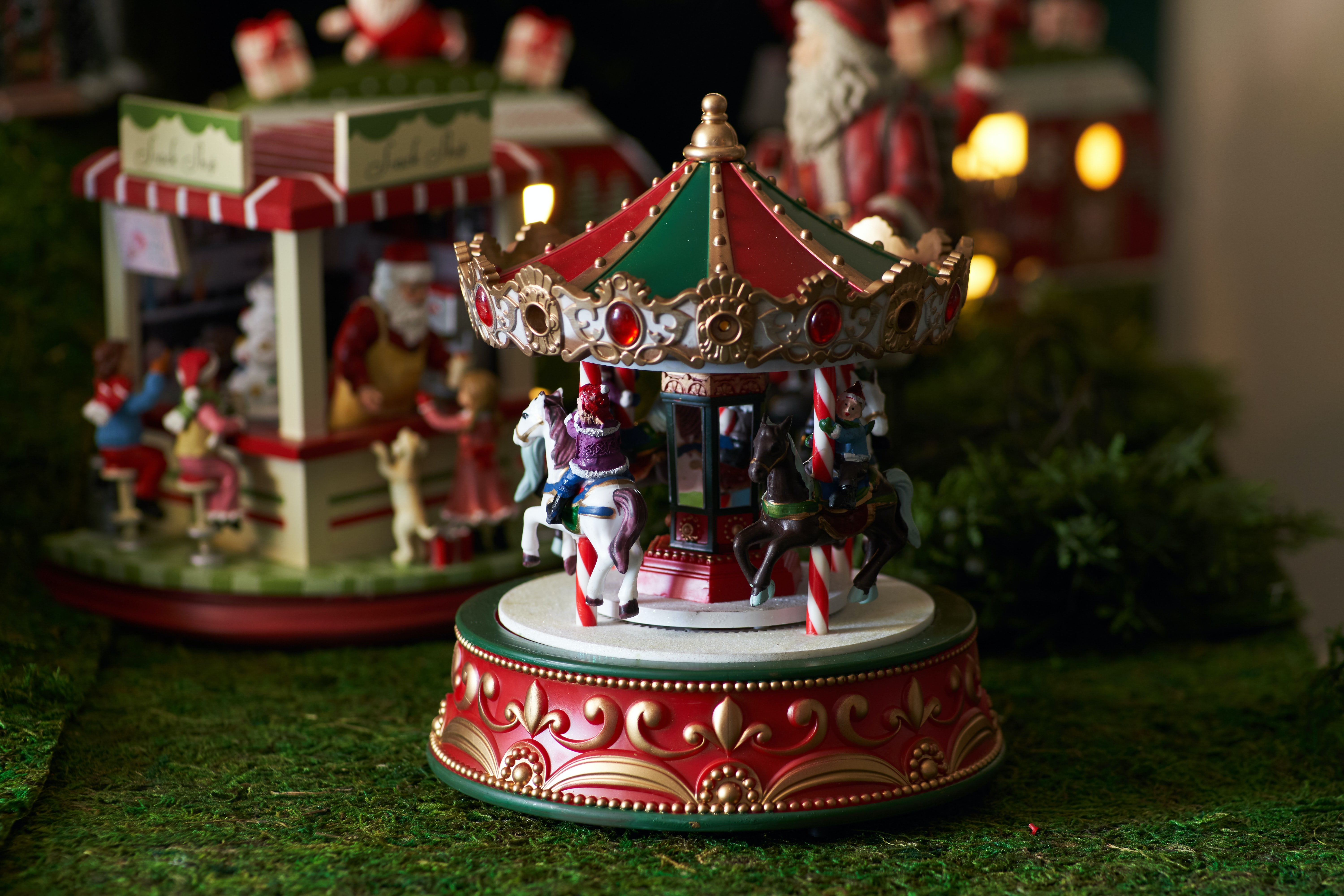 selective focus photography of white and multicolored ceramic carousel figurine on green surface