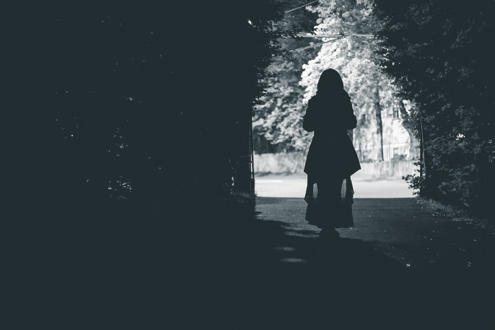 silhouette of woman walking at the pathway