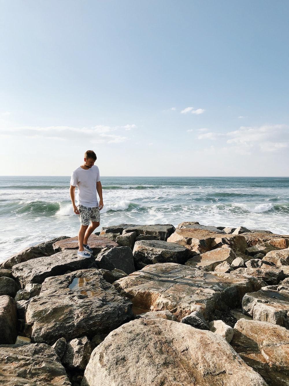 man standing on rocks near body of water