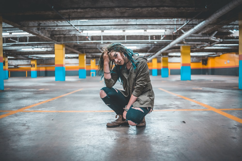woman touching her hair sitting on parking lot
