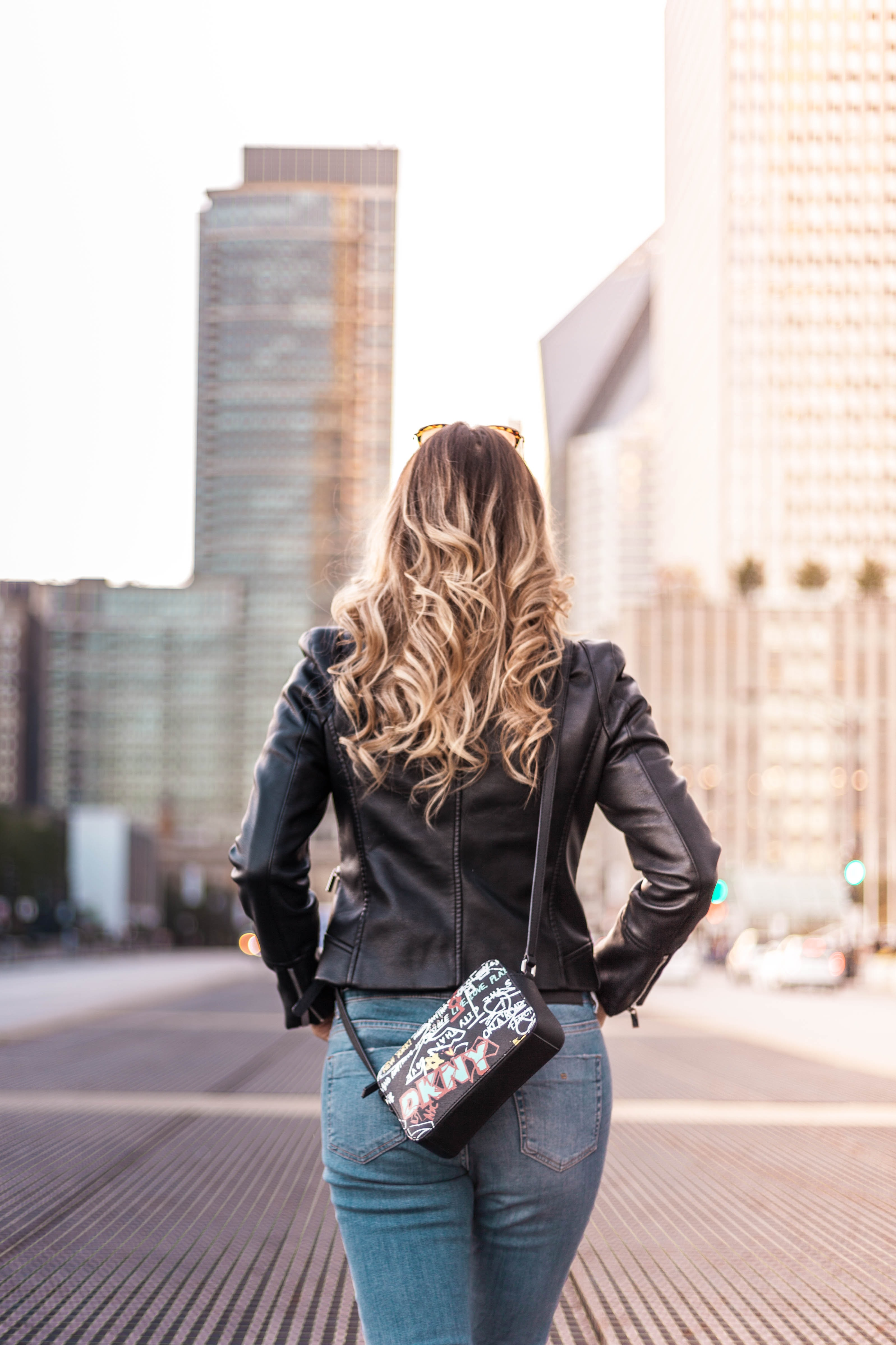 woman wearing black leather jacket and blue denim bottoms standing on gray concrete surface near buildings during daytime