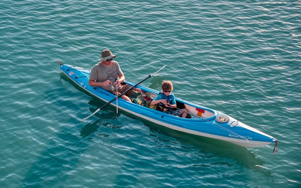 man and boy riding on kayak