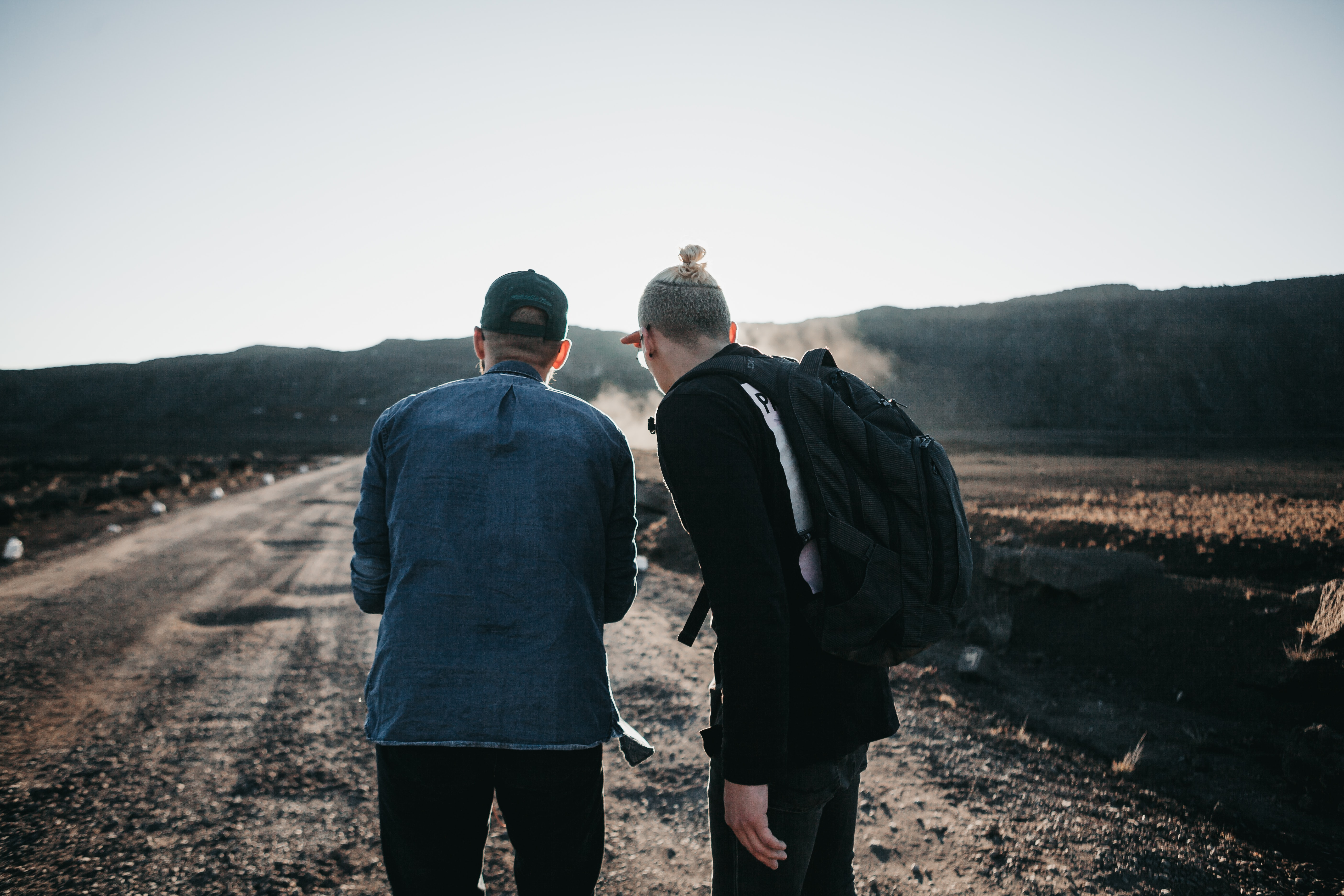 two men standing on brown pathway