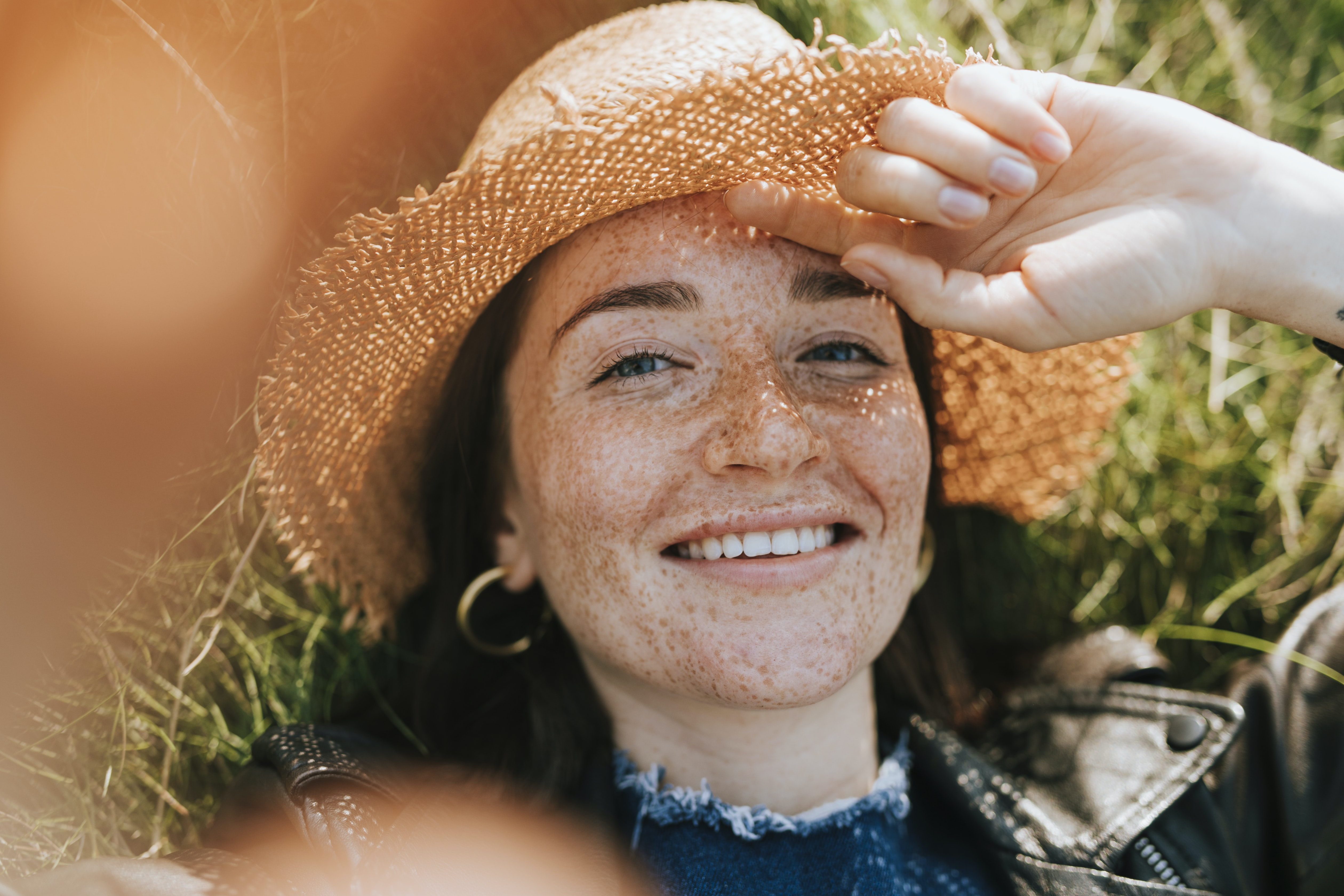woman wearing sun hat while lying on grass
