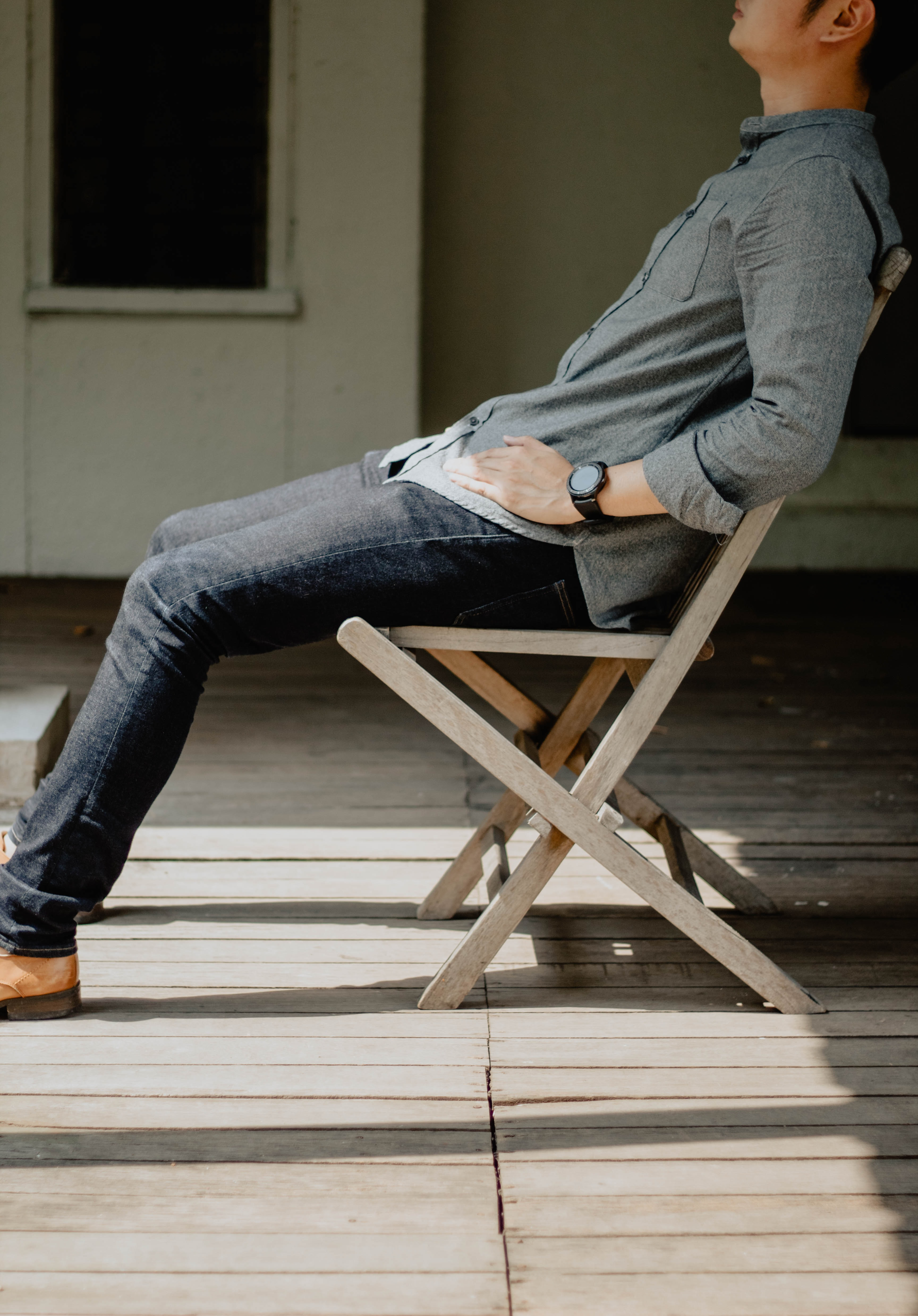 man sitting on brown wooden chair
