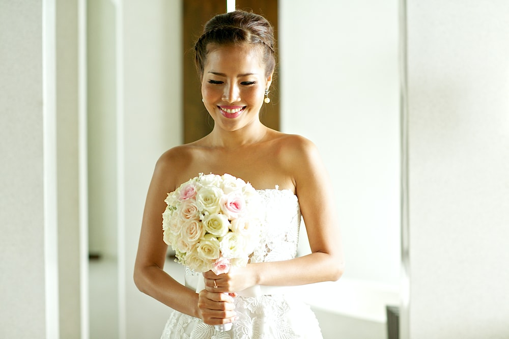 woman wearing white tube dress holding bouquet of flower