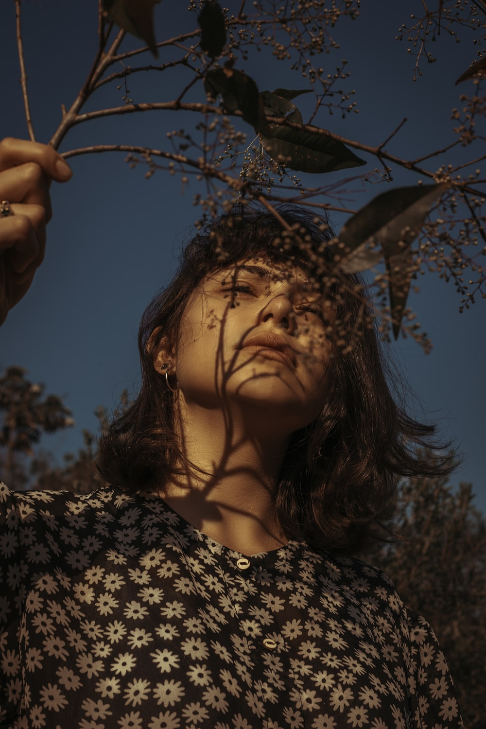 low-angle photo of woman holding tree wig