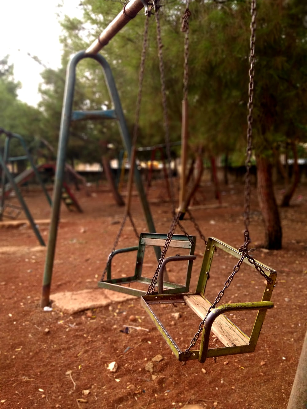 green and brown swing playground