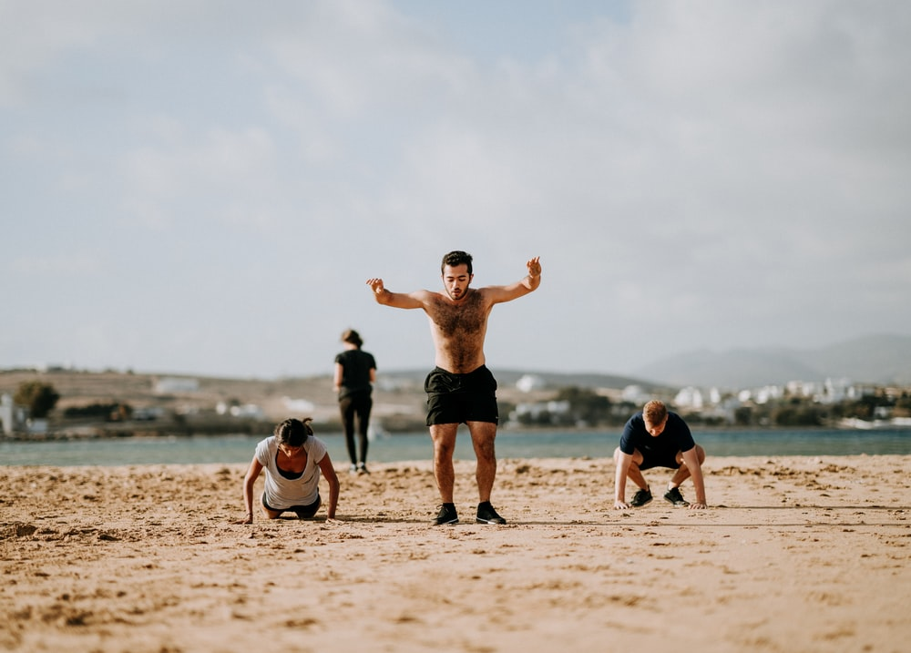 people doing exercise on beach front