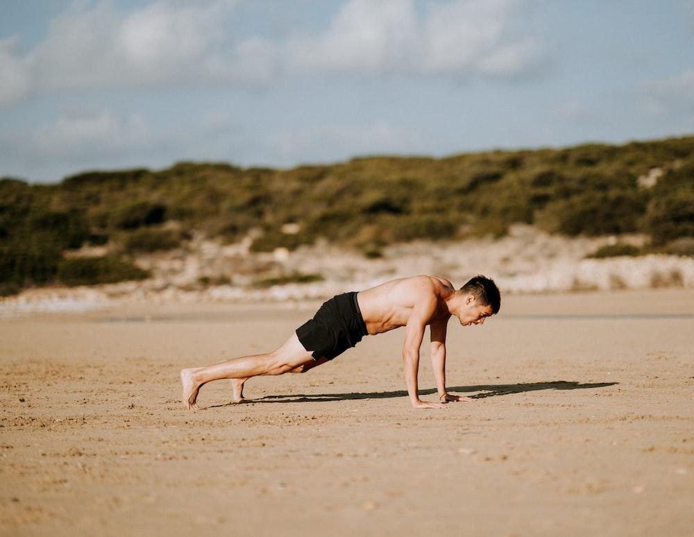 man doing push up on sand