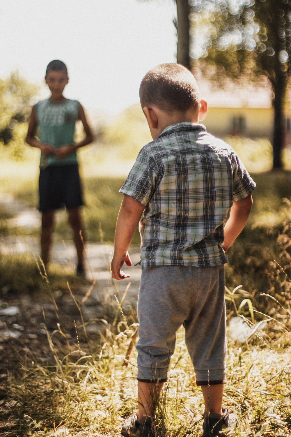 selective focus photography of boy standing on grass in a distance of boy standing under shade of tree at daytime