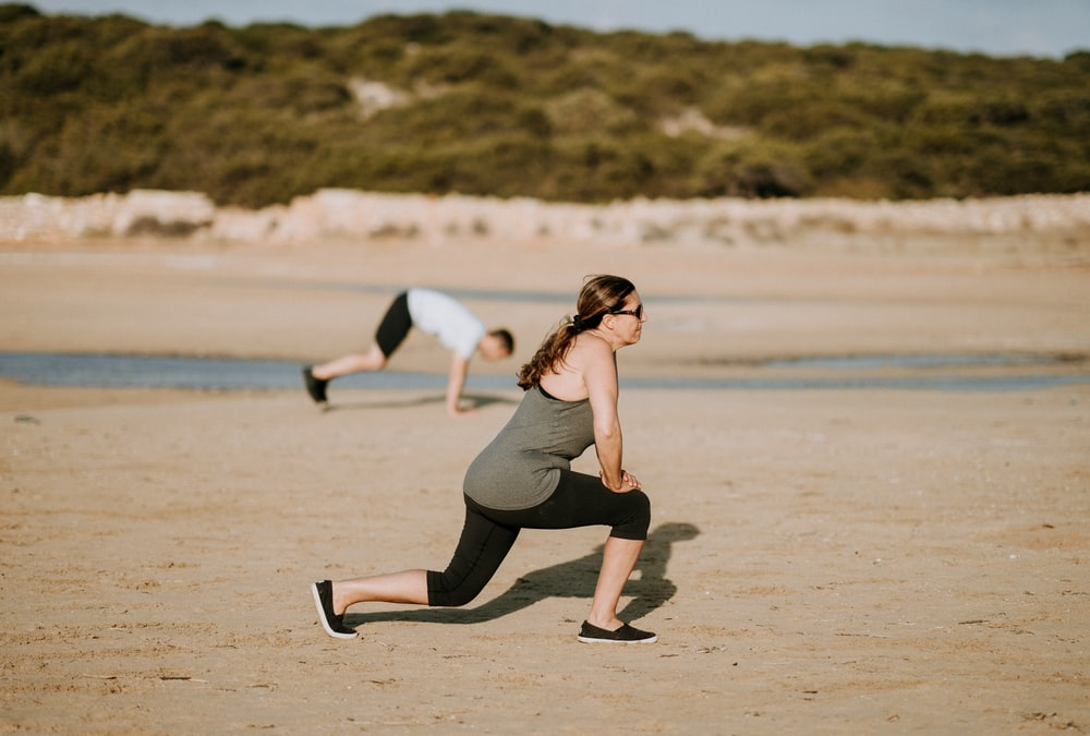 woman wearing grey tank top doing exercise