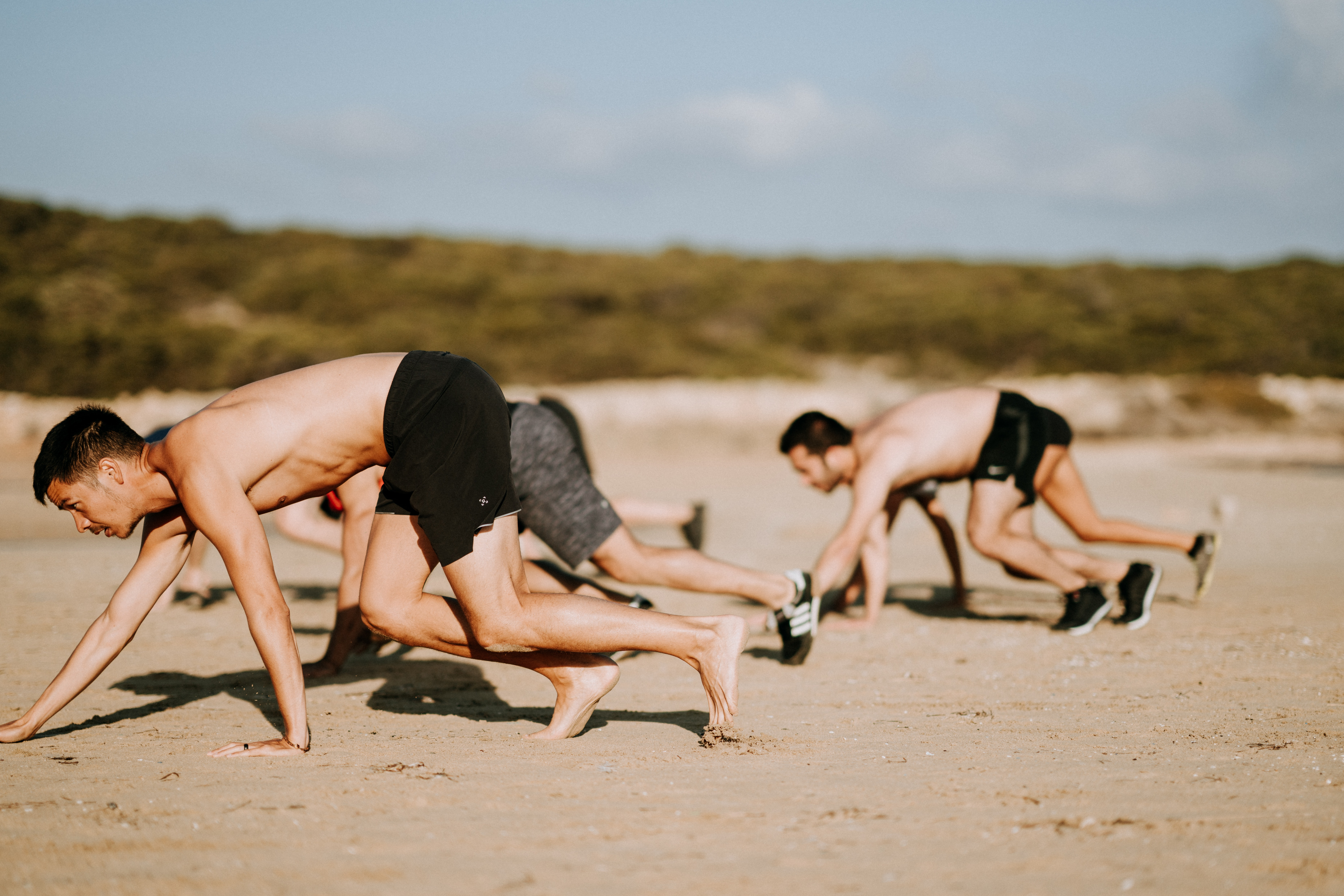 group of men crawling at sand covered ground