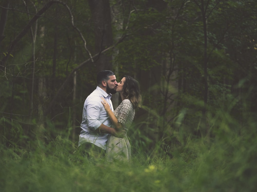kissing man and woman standing on green grass field