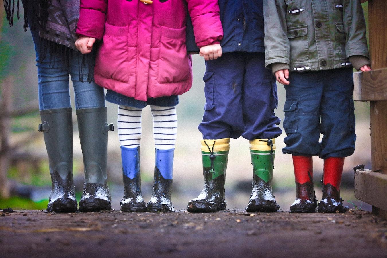 Four children wearing rain boots