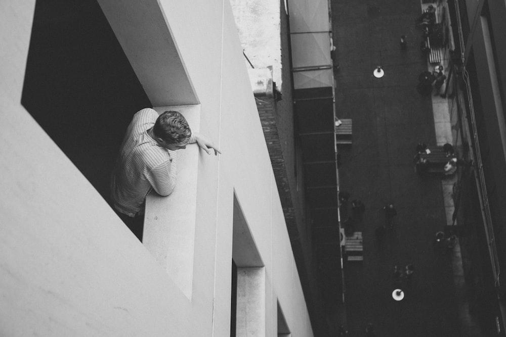 grayscale photo of man beside window