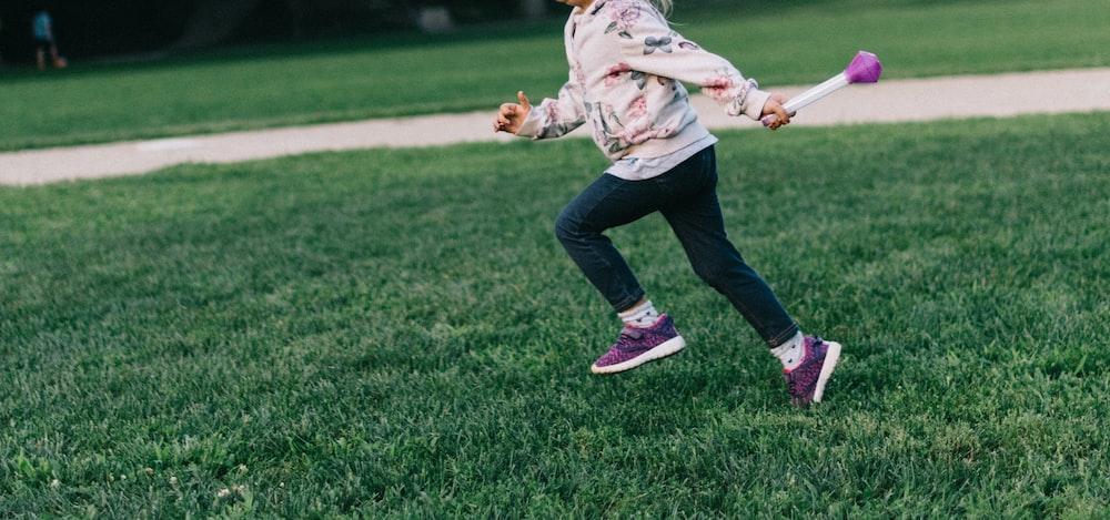 girl running on green field