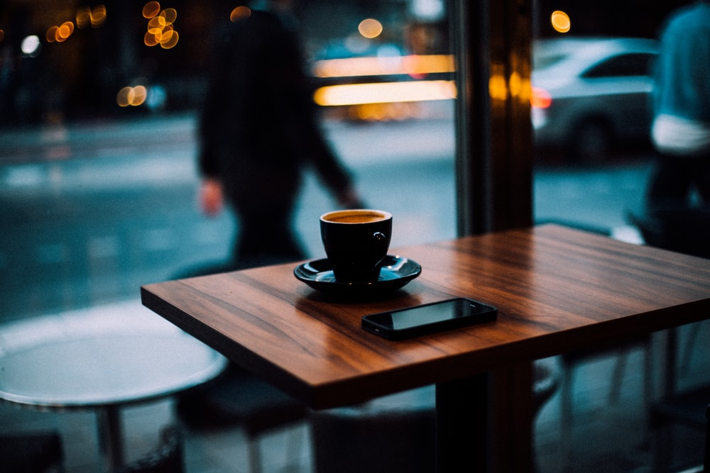 cup of coffee and smartphone on top of wooden dining table