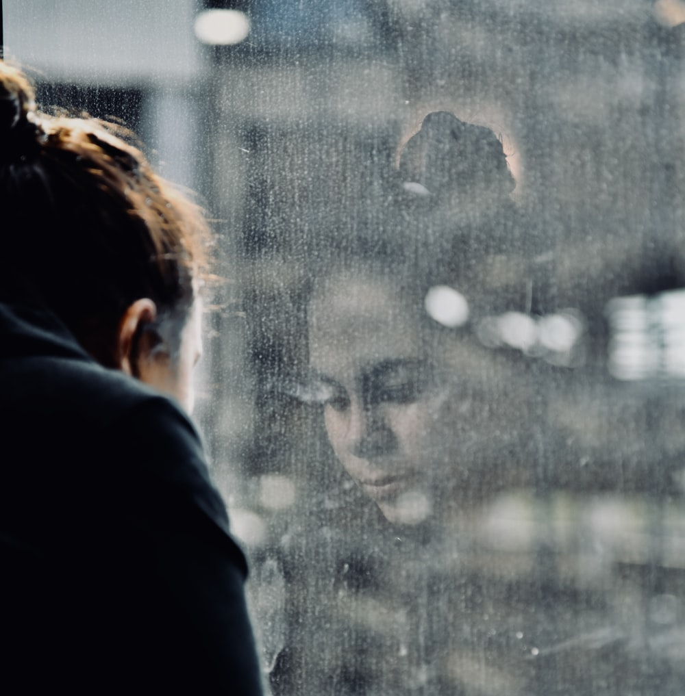 woman standing beside glass wall
