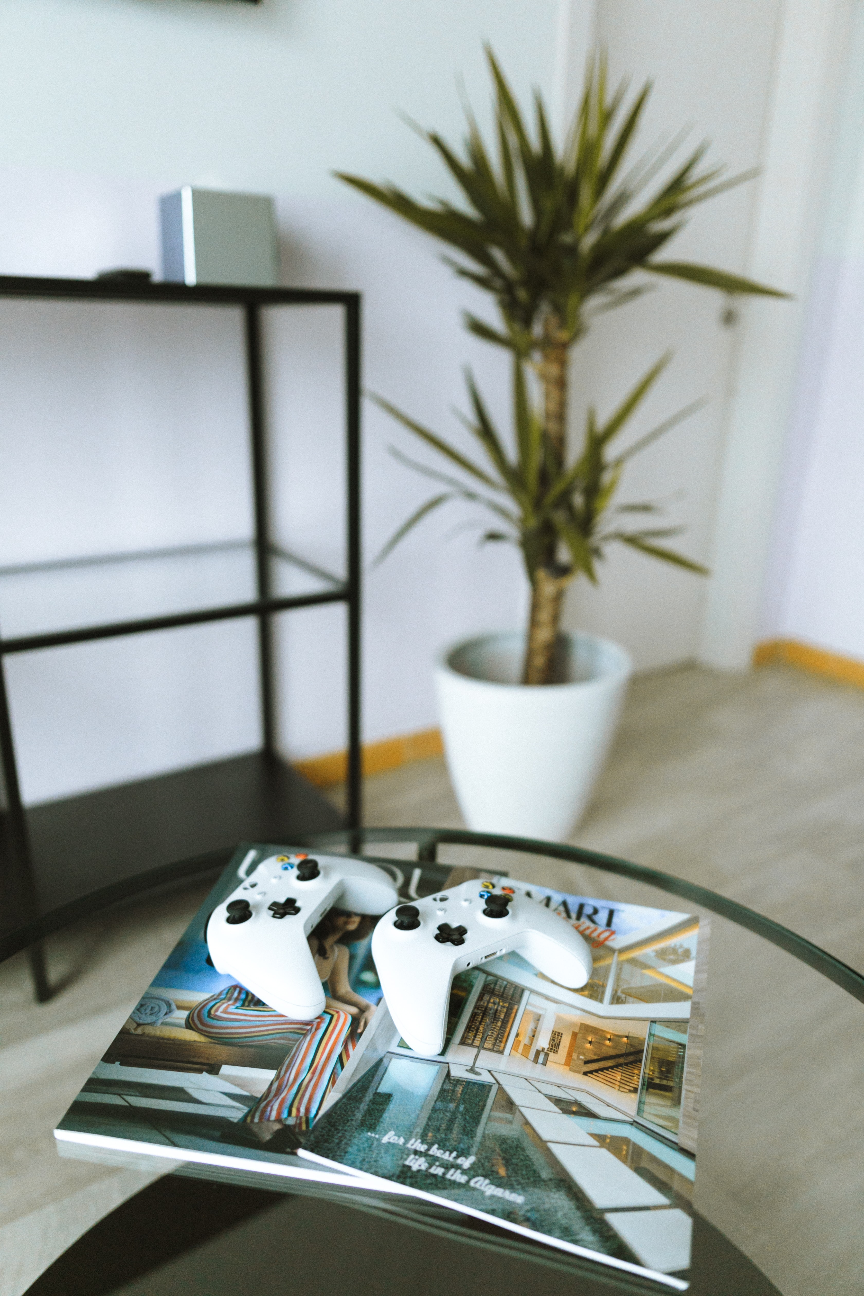 two Xbox One game controllers on magazine book on top of glass table