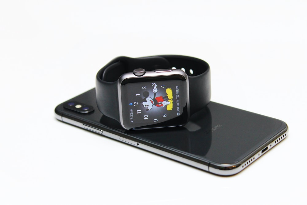 Apple Watch on top of space gray iPhone X