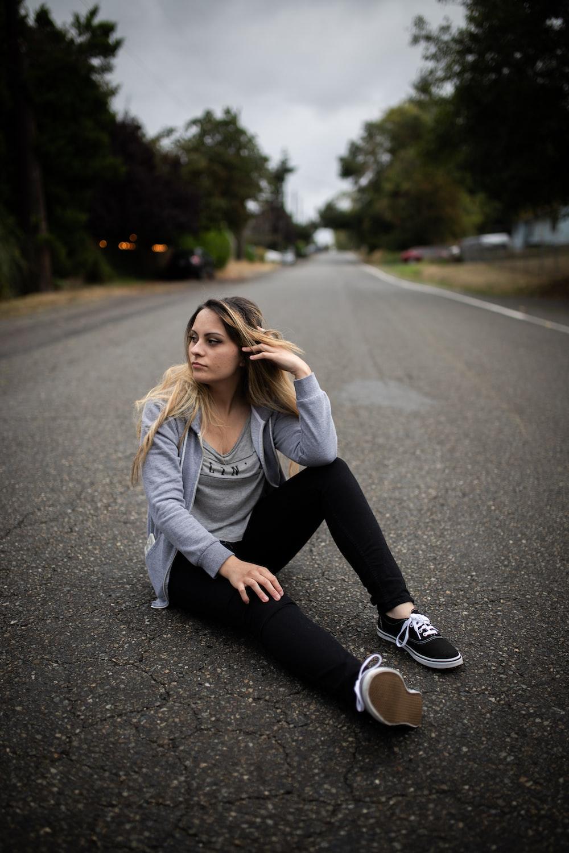 woman sitting on empty road