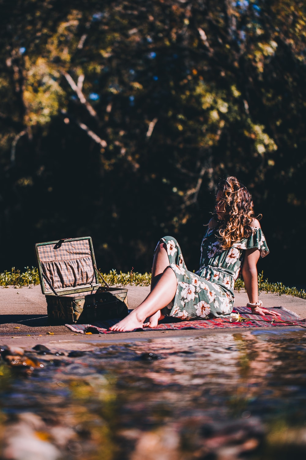 woman sitting beside river
