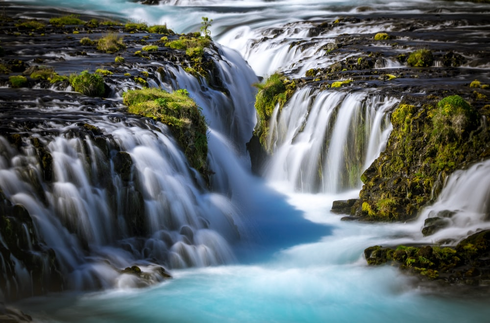 time lapse photography of flowing multi-tier waterfall