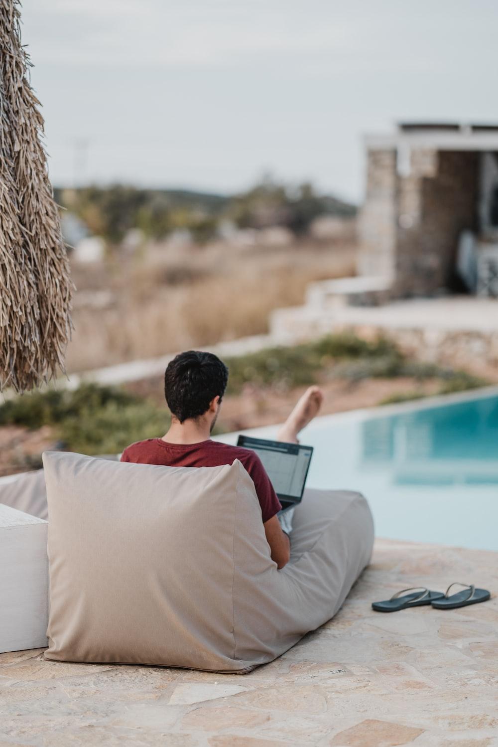 man sitting on lounger while using laptop