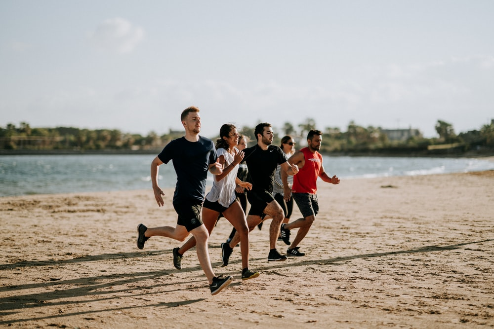 men and women running on sea shore