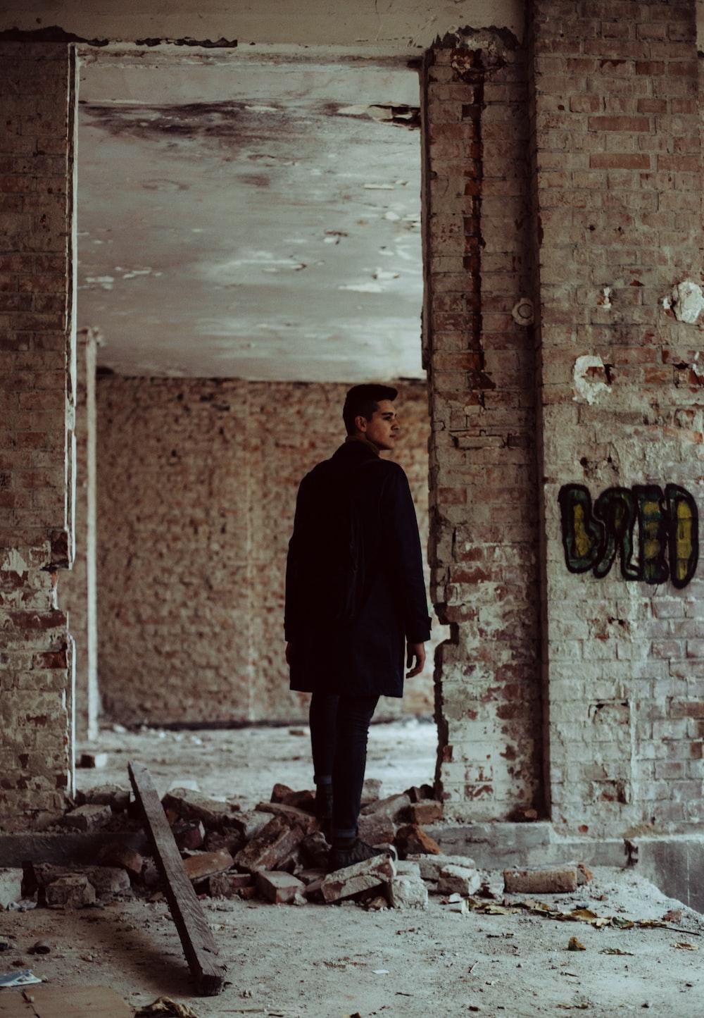 man wearing black suit walking in abandoned building
