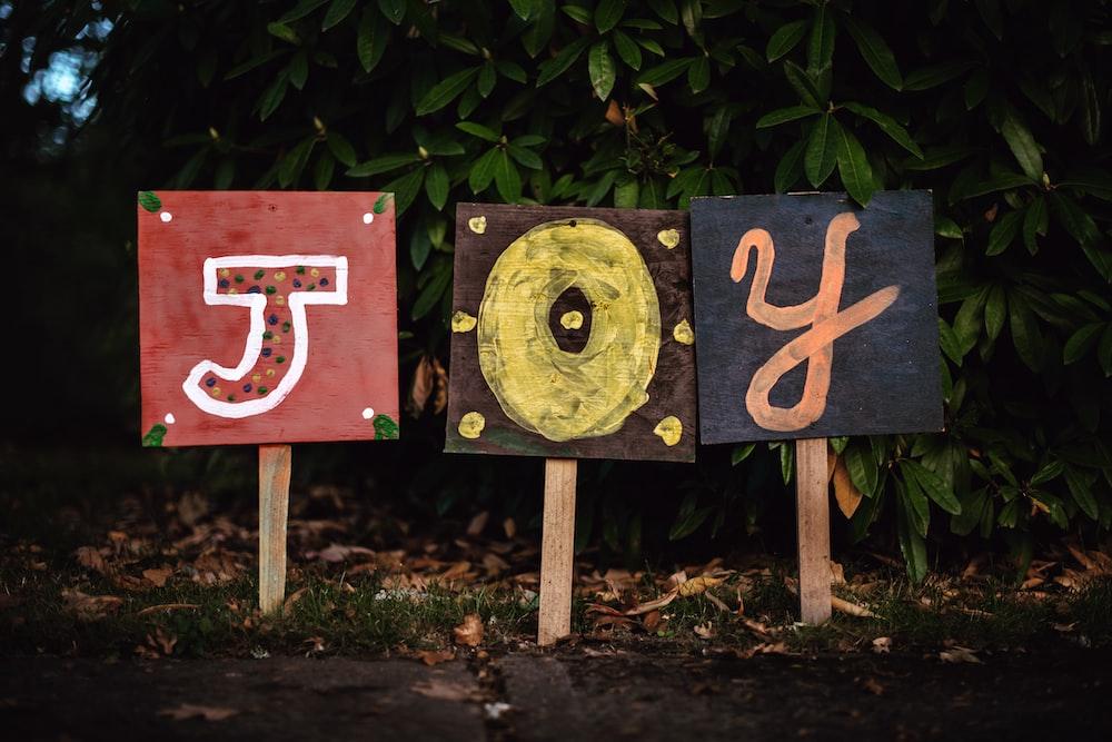 three assorted-color joy signage