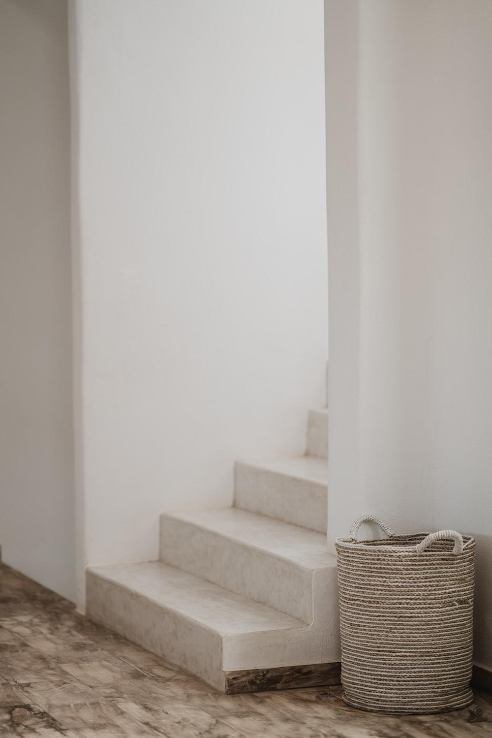 gray wicker basket beside stair