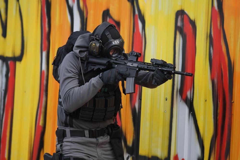 man in full gear holding gun